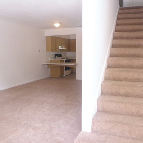 Carpeted staircase and empty living room with kitchen in the background.