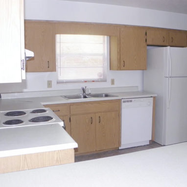 Kitchen with white appliances and light brown wooden cabinetry.